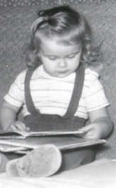 Author Sybil Johnson as child, age 2, looking at books